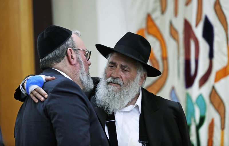 Rabbi Yishoel Goldstein, right, greets an attendee at the funeral for Lori Kaye, who was killed Saturday when a gunman opened fire inside the Chabad of Poway synagogue in Poway, Calif. (AP Photo/Gregory Bull)
