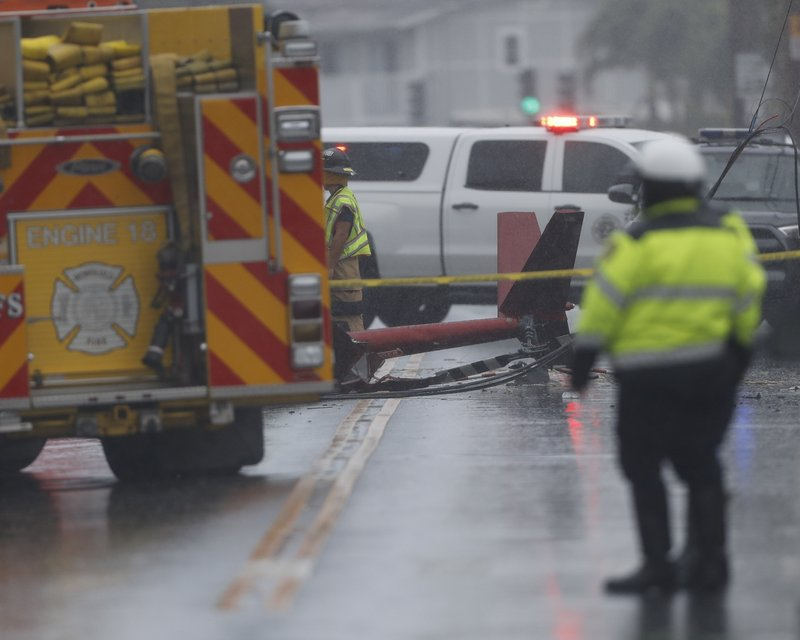 The tail of a crashed helicopter is seen in the middle of the street, Monday, April 29, 2019, in Kailua, Hawaii. A helicopter crashed in the middle of the Kailua neighborhood killing three people. (AP Photo/Marco Garcia)
