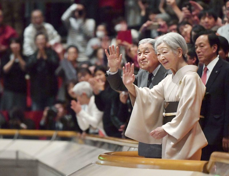 In this Jan. 20, 2019, photo,  Japanese Emperor Akihito, front left, and Empress Michiko, front right,  acknowledge the crowd during their visit to the New Year Grand Sumo Tournament at Ryogoku Kokugikan in Tokyo. (Kyodo News via AP)