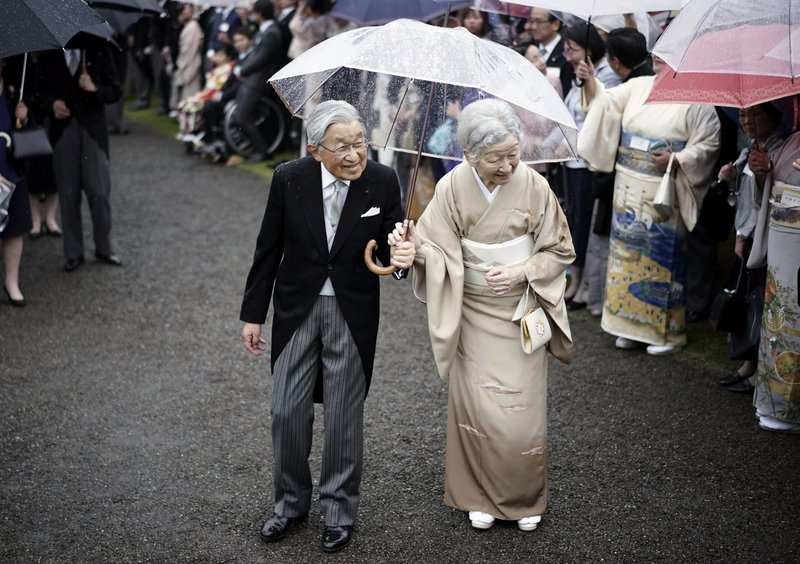 FILE - In this Nov. 9, 2018, file photo, Japan's Emperor Akihito, left, and Empress Michiko, right, greet the guests during the autumn garden party at the Akasaka Palace imperial garden in Tokyo. (AP Photo/Eugene Hoshiko, File)
