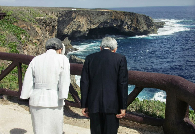 FILE - In this June 28, 2005, file photo, Emperor Akihito, right, accompanied by Empress Michiko bow to the infamous Banzai Cliff, or Puntan Sabaneta, in Saipan, to offer prayers for the Japanese soldiers and civilians who jumped off the rocky cliff 60 years ago to avoid being captured by the U. (Eriko Sugita/U.S. Pool Photo via AP, File)
