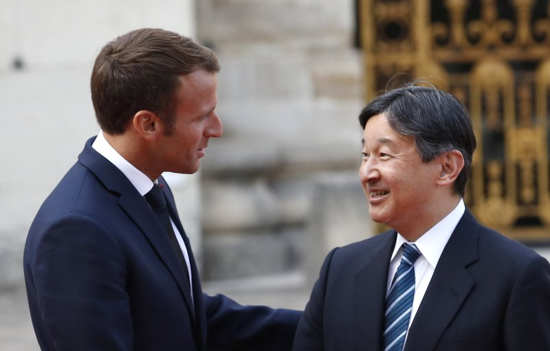 FILE - In this Sept. 12, 2018, file photo, Japan's Crown Prince Naruhito, right, is greeted by French President Emmanuel Macron before a meeting at the Chateau de Versailles, west of Paris. (AP Photo/Christophe Ena, File)