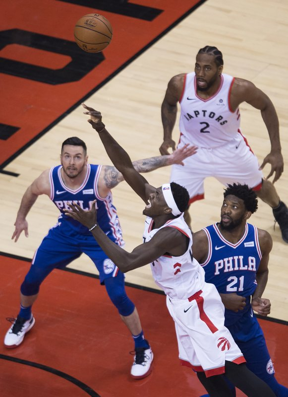 Toronto Raptors forward Pascal Siakam, center, drives to the bet past Philadelphia 76ers guard JJ Redick, left, and Philadelphia 76ers center Joel Embiid (21) during the second half of a second-round NBA basketball playoff game in Toronto, Monday, April 29, 2019. (Nathan Denette/The Canadian Press via AP)