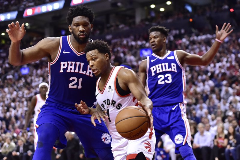 Toronto Raptors guard Kyle Lowry (7) drives around Philadelphia 76ers center Joel Embiid (21) during second-half, second-round NBA basketball playoff action in Toronto, Monday, April 29, 2019. (Frank Gunn/The Canadian Press via AP)
