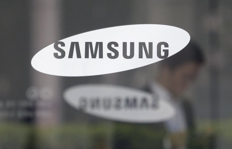 An employee walks past a logo of the Samsung Electronics Co. at its office in Seoul, South Korea, Tuesday, April 30, 2019. Samsung Electronics Co. says its operating profit for the last quarter declined more than 60% from a year earlier because of falling chip prices and sluggish demands for its display panels. (AP Photo/Ahn Young-joon)