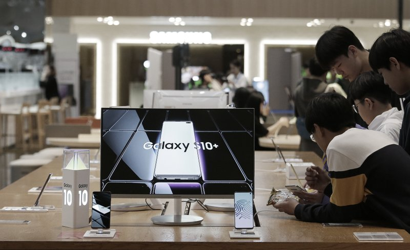 Middle school students try out Samsung Electronics' Galaxy S10+ smartphones at its shop in Seoul, South Korea, Tuesday, April 30, 2019. Samsung Electronics Co. says its operating profit for the last quarter declined more than 60% from a year earlier because of falling chip prices and sluggish demands for its display panels. (AP Photo/Ahn Young-joon)