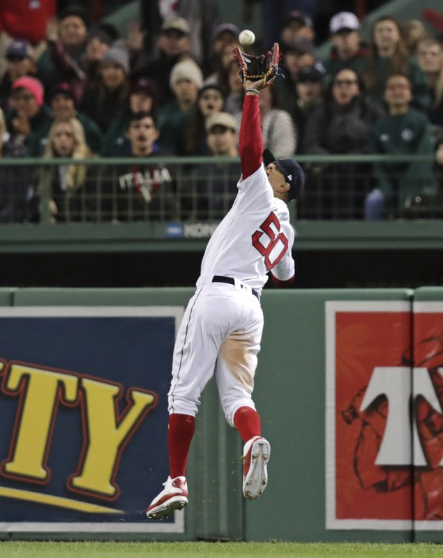 Boston Red Sox right fielder Mookie Betts leaps to make the catch of a fly-out by Oakland Athletics' Chad Pinder during the eighth inning of a baseball game at Fenway Park, Monday, April 29, 2019, in Boston. (AP Photo/Charles Krupa)