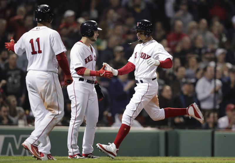 Boston Red Sox's Mookie Betts, right, is congratulated by Andrew Benintendi, center, after they both scored on a two RBI double by Xander Bogaerts off Oakland Athletics starting pitcher Frankie Montas during the third inning of a baseball game at Fenway Park, Monday, April 29, 2019, in Boston. At left is Boston Red Sox's Rafael Devers (11.(AP Photo/Charles Krupa)