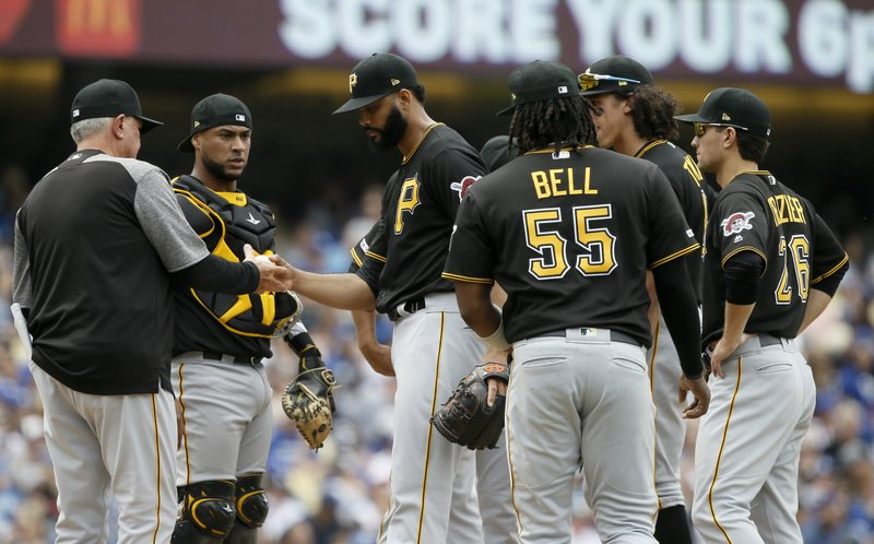 Pittsburgh Pirates manager Clint Hurdle, left, takes out relief pitcher Richard Rodriguez, third from left, with catcher Elias Diaz, second from left, and the infield watching during the seventh inning of a baseball game against the Los Angeles Dodgers in Los Angeles, Sunday, April 28, 2019. (AP Photo/Alex Gallardo)