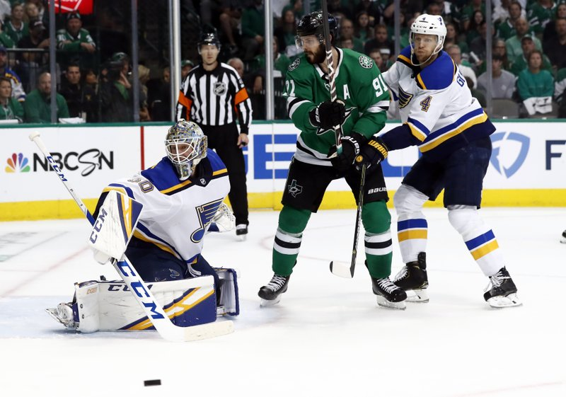 St. Louis Blues goaltender Jordan Binnington (50) watches the puck slide past alongside teammate Carl Gunnarsson (4) and Dallas Stars' Tyler Seguin (91) during the first period in Game 3 of an NHL second-round hockey playoff series, Monday, April 29, 2019, in Dallas. (AP Photo/Tony Gutierrez)