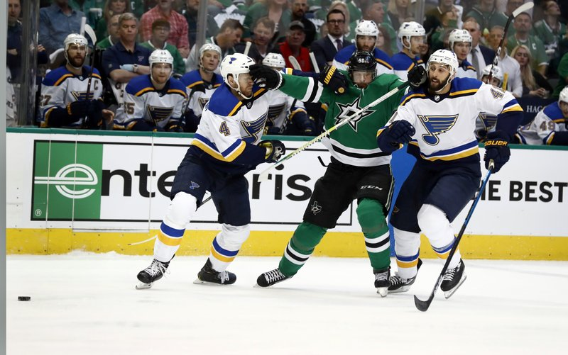 Dallas Stars' Jason Spezza, center, squeezes between St. Louis Blues' Carl Gunnarsson (4), of Sweden, and Robert Bortuzzo while chasing the puck during the first period in Game 3 of an NHL second-round hockey playoff series, Monday, April 29, 2019, in Dallas. (AP Photo/Tony Gutierrez)