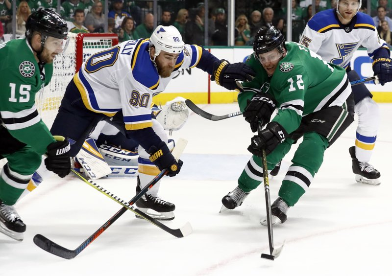 St. Louis Blues' Ryan O'Reilly (90) reaches for the puck between Dallas Stars' Blake Comeau (15) and Radek Faksa (12) during the first period in Game 3 of an NHL second-round hockey playoff series, Monday, April 29, 2019, in Dallas. (AP Photo/Tony Gutierrez)
