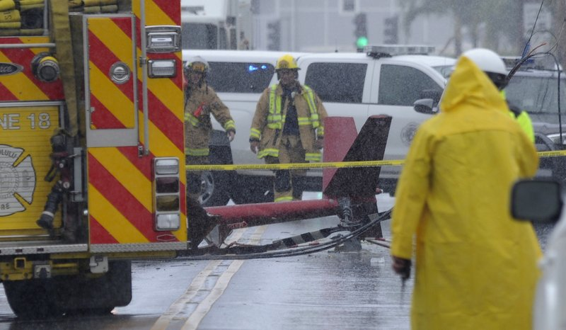 A portion of the tail section of a helicopter is shown after crashing in Kailua, Hawaii, Monday, April 29, 2019. Fire and helicopter parts rained from the sky Monday in a suburban Honolulu community in a crash that killed three people aboard, officials and witnesses said. (Bruce Asato/Honolulu Star-Advertiser via AP)