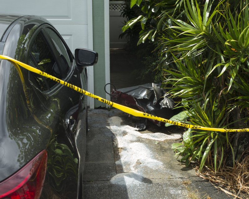 Debris lies on the ground where parts of a helicopter hit a parked car, Monday, April 29, 2019, in Kailua, Hawaii. Fire and helicopter parts rained from the sky Monday in a suburban Honolulu community in a crash that killed three people aboard, officials and witnesses said.  (AP Photo/Marco Garcia)