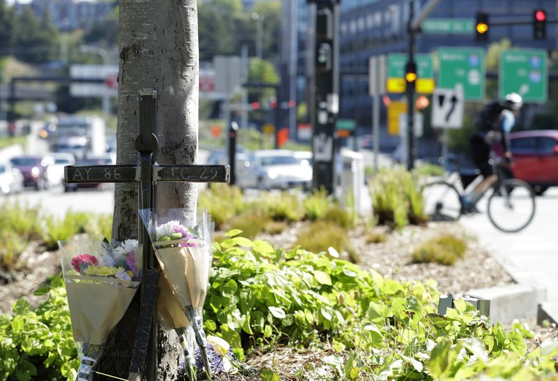 An iron cross bearing the numbers of Ironworkers Local union chapters from Portland and Seattle stands next to flowers, Monday, April 29, 2019, in Seattle at a memorial on a median across the street from where a construction crane collapsed and fell Saturday, killing four people, two of whom were ironworkers. (AP Photo/Ted S. Warren)