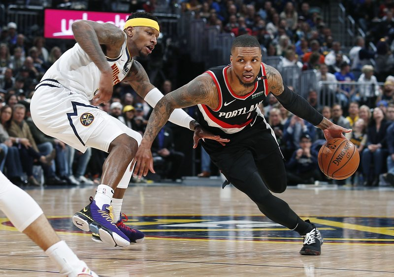 Portland Trail Blazers guard Damian Lillard, right, drives past Denver Nuggets forward Torrey Craig in the second half of Game 1 of an NBA basketball second-round playoff series, Monday, April 29, 2019, in Denver. The Nuggets won 121-113. (AP Photo/David Zalubowski)