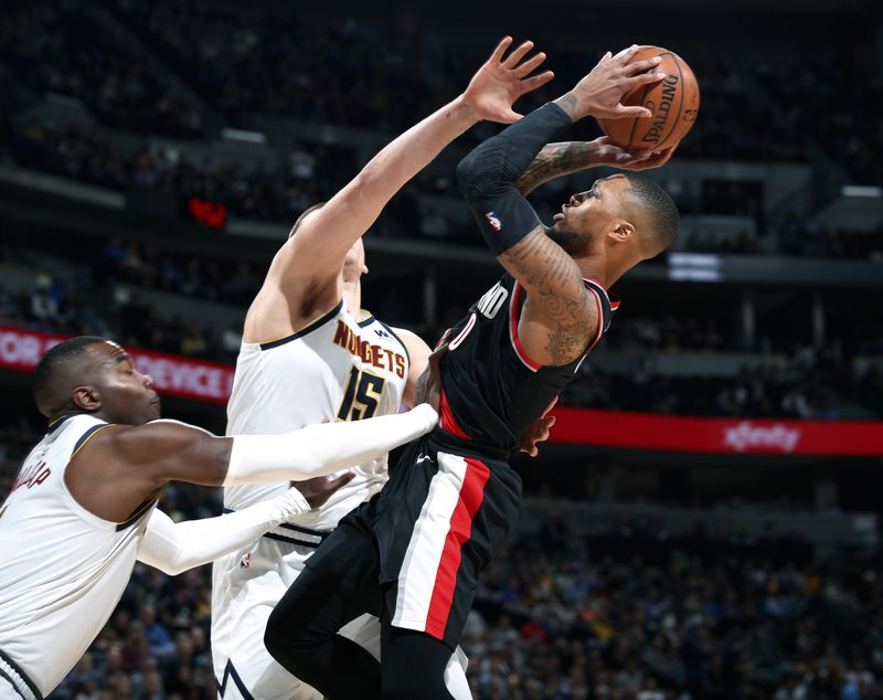 Portland Trail Blazers guard Damian Lillard, right, shoots as Denver Nuggets center Nikola Jokic and forward Paul Millsap, left, defend in the second half of Game 1 of an NBA basketball second-round playoff series, Monday, April 29, 2019, in Denver. The Nuggets won 121-113. (AP Photo/David Zalubowski)