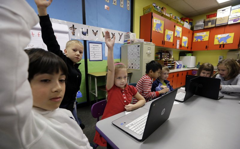 FILE - In this file photo taken Nov. 4, 2015, kindergartner Lauren Meek, third left, raises her hand as she sits with second grade students helping her on programming during their weekly computer science lesson at Marshall Elementary School in Marysville, Wash. Though less likely to study in a formal technology or engineering course, America's girls are showing more mastery of those subjects than their boy classmates, according to newly released national education data made public Tuesday, April 30, 2019. (AP Photo/Elaine Thompson, File)