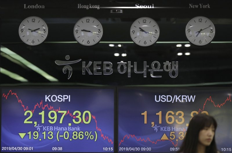 A currency trader walks by screens showing the Korea Composite Stock Price Index (KOSPI), left, and the foreign exchange rate between U.S. dollar and South Korean won at the foreign exchange dealing room in Seoul, South Korea, Tuesday, April 30, 2019. Asian stock markets were mixed Tuesday after Wall Street hit a new high and Chinese factory grew in April but below the previous month's pace. (AP Photo/Lee Jin-man)