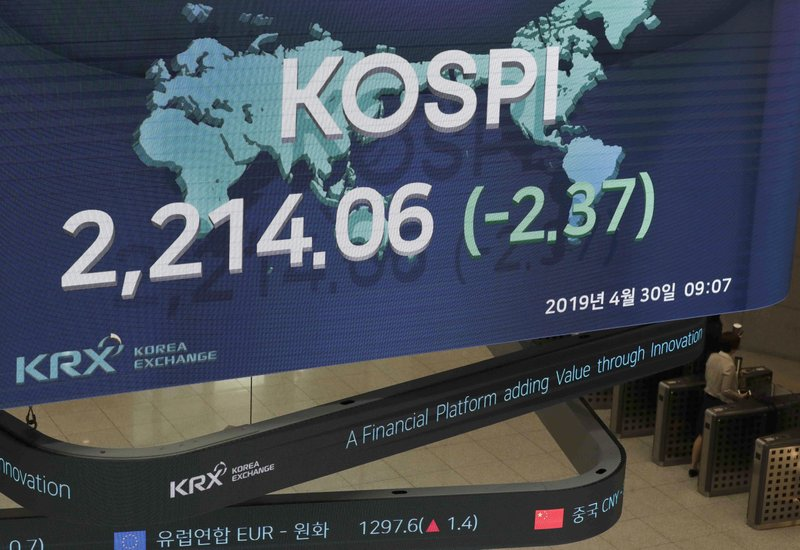 A woman walks near under a screen showing the Korea Composite Stock Price Index (KOSPI) at the Korea Exchange in Seoul, South Korea, Tuesday, April 30, 2019. Asian stock markets were mixed Tuesday after Wall Street hit a new high and Chinese factory grew in April but below the previous month's pace. (AP Photo/Lee Jin-man)