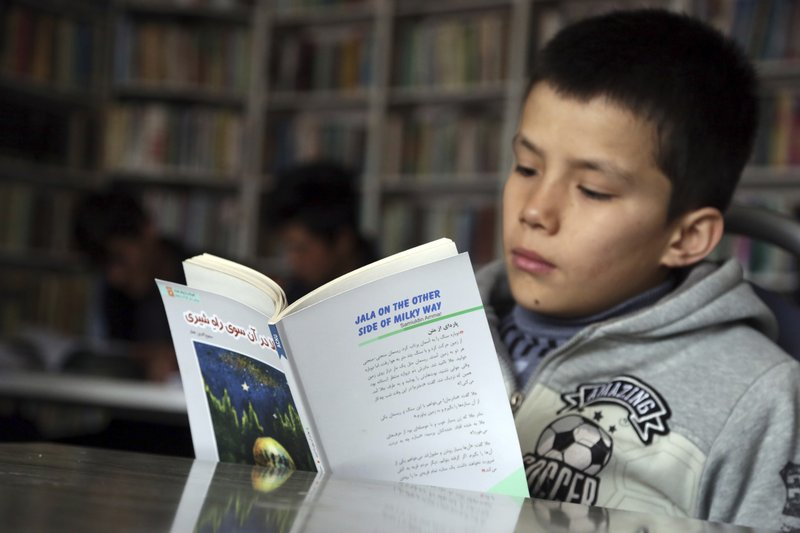 In this Tuesday, March 19, 2019, an Afghan boy studies at the Rahila library, in Kabul, Afghanistan. Launched in February by the Afghanistan Human Rights and Democracy Organization, the center seeks to salvage, protect and share memories and stories of civilian victims of the country's four decades of war. (AP Photo/Rahmat Gul)