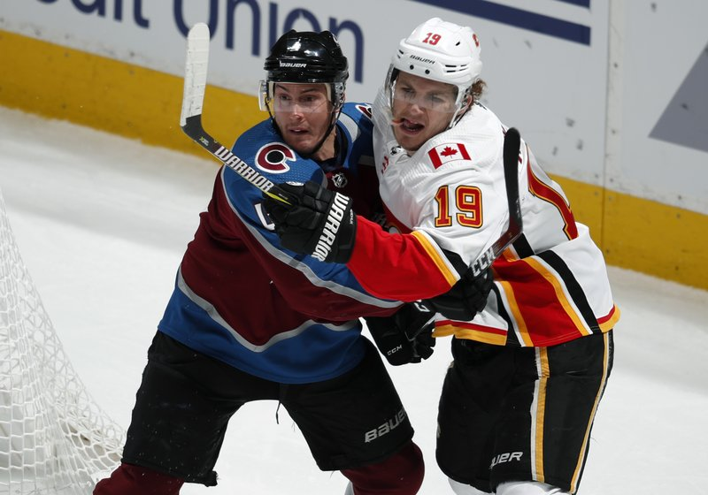 Colorado Avalanche defenseman Tyson Barrie, left, jostles for position by the net with Calgary Flames left wing Matthew Tkachuk during the first period of Game 4 of an NHL hockey playoff series Wednesday, April 17, 2019, in Denver. (AP Photo/David Zalubowski)
