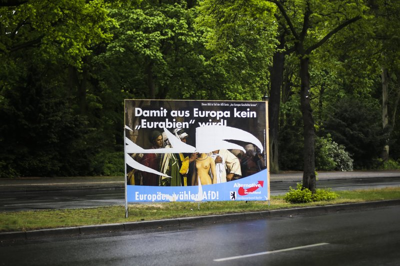 In this Monday, April 29, 2019 photo, an destroyed election campaign poster of the German Alternative fuer Deutschland (Alternative for Germany), AfD, party displayed at a road in Berlin, Germany. The poster for the European Parliament elections shows the painting 'Slave Market' from 1866 by the french artist Jean-Leon Gerome. The US museum 'The Clark Art Insitiute' in Williamstown, MA, owner of the painting, has asked the German far right party AfD not to use the picture any more. Top slogan reads 'So that Germany does not become an 'Eurabia'!. (AP Photo/Markus Schreiber)