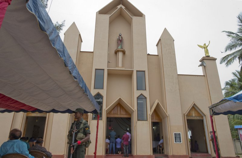 A soldier stands guard during a Catholic Mass outside St. Joseph's church in Thannamunai, Sri Lanka, Tuesday, April 30, 2019. This small village in eastern Sri Lanka has held likely the first Mass since Catholic leaders closed all their churches for fear of more attacks after the Easter suicide bombings that killed over 250 people. (AP Photo/Gemunu Amarasinghe)