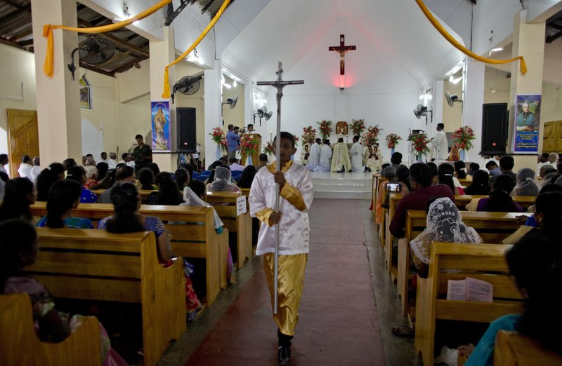A boy holds a processional cross during Mass at St. Joseph's church in Thannamunai, Sri Lanka, Tuesday, April 30, 2019. This small village in eastern Sri Lanka has held likely the first Mass since Catholic leaders closed all their churches for fear of more attacks after the Easter suicide bombings that killed over 250 people. (AP Photo/Gemunu Amarasinghe)