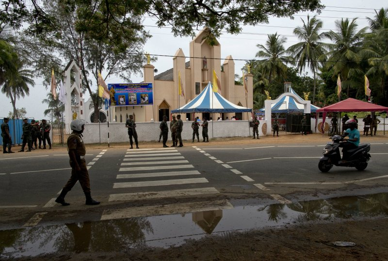 Soldiers guard outside St. Joseph's church, Tuesday, April 30, 2019, in Thannamunai, Sri Lanka. This small village in eastern Sri Lanka has held likely the first Mass since Catholic leaders closed all their churches for fear of more attacks after the Easter suicide bombings that killed over 250 people. (AP Photo/Gemunu Amarasinghe)
