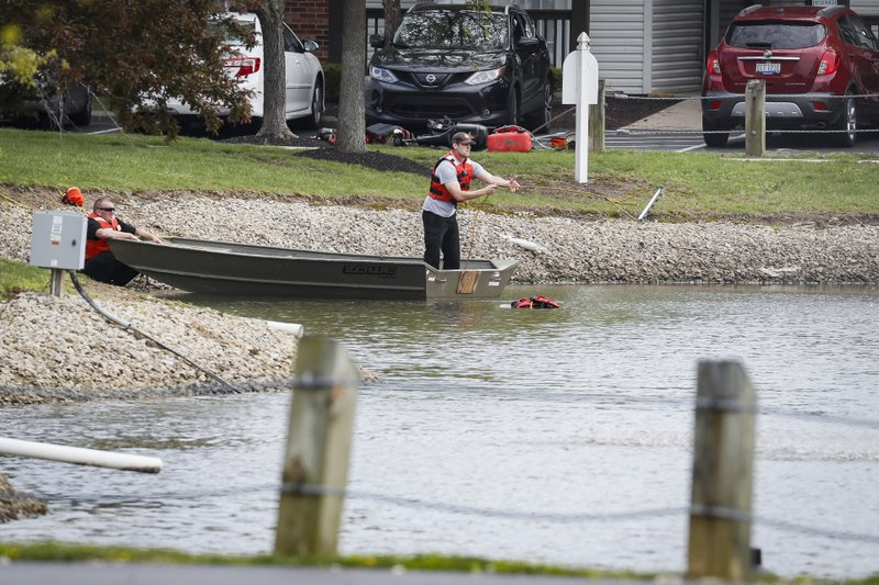 Police authorities search a nearby pond at a scene at an apartment complex Monday, April 29, 2019, in West Chester, Ohio. Several people were found dead at the apartment complex where multiple gunshots were fired, police said Monday. No suspect has been identified. (AP Photo/John Minchillo)