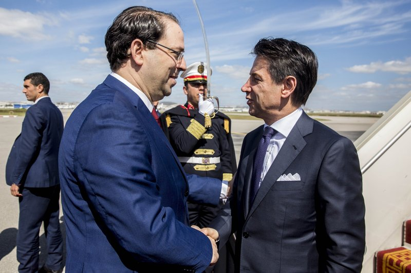 Tunisian Prime Minister Youssef Chahed, left, welcomes Italian Prime Minister Giuseppe Conte, upon his arrival at Carthage airport, as part of an inter-governmental summit in Tunis, Tuesday, April 30, 2019. Italy's chief of government and an array of top ministers are visiting Tunisia, a leading strategic and economic partner whose shared concerns include migration and the North African country's unstable neighbor, Libya. (AP Photo/Hassene Dridi)