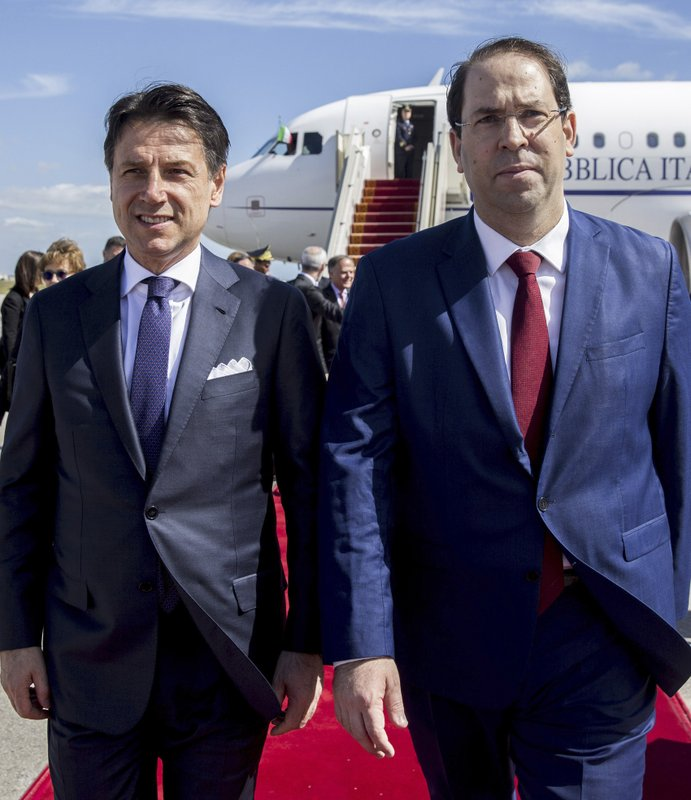 Tunisian Prime Minister Youssef Chahed, right, welcomes Italian Prime Minister Giuseppe Conte, upon his arrival at Carthage airport, as part of an inter-governmental summit in Tunis, Tuesday, April 30, 2019. Italy's chief of government and an array of top ministers are visiting Tunisia, a leading strategic and economic partner whose shared concerns include migration and the North African country's unstable neighbor, Libya. (AP Photo/Hassene Dridi)