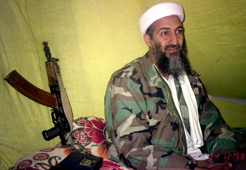 FILE - In this Dec. 24, 1998, file photo, al-Qaida leader Osama Bin Laden speaks to a selected group of reporters in mountains of Helmand province in southern Afghanistan. When the reclusive Islamic State group leader Abu Bakr al-Baghdadi  appeared in a video Monday, he was the latest in a series of most-wanted figures, to use the medium to communicate with the outside world. Al-Baghdadi in his latest video mirrored a picture of Osama Bin Laden in his videos, sitting cross-legged with an assault rifle kept against the wall next to him. (AP Photo/Rahimullah Yousafzai, File)
