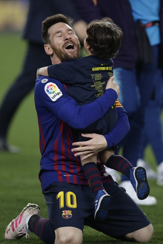 Barcelona forward Lionel Messi celebrates with his son winning the Spanish League title, at the end of the Spanish La Liga soccer match between FC Barcelona and Levante at the Camp Nou stadium in Barcelona, Spain, Saturday, April 27, 2019. Barcelona clinched the Spanish La Liga title, with three matches to spare, after it defeated Levante 1-0. (AP Photo/Manu Fernandez)