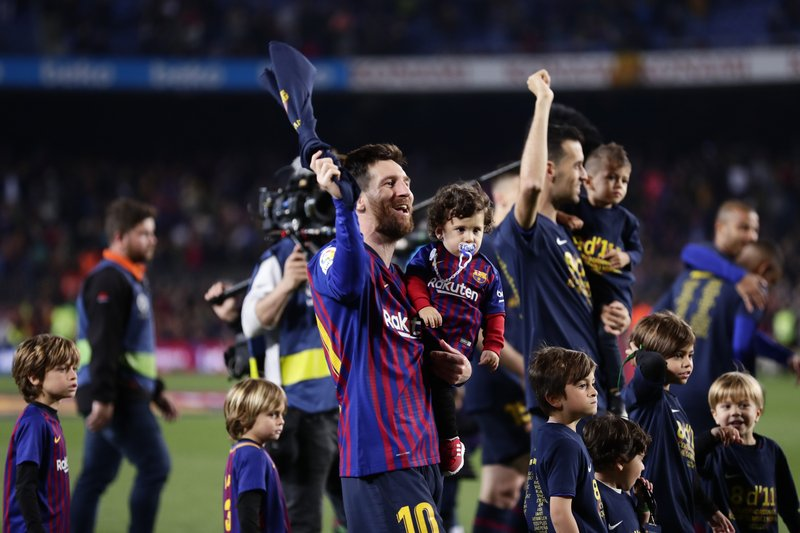 Barcelona forward Lionel Messi, left, and Barcelona midfielder Sergio Busquets, with their children, celebrate winning the Spanish League title, at the end of the Spanish La Liga soccer match between FC Barcelona and Levante at the Camp Nou stadium in Barcelona, Spain, Saturday, April 27, 2019. Barcelona clinched the Spanish La Liga title, with three matches to spare, after it defeated Levante 1-0. (AP Photo/Manu Fernandez)