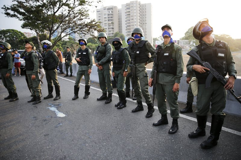 Uprising soldiers stands outside La Carlota air base in Caracas, Venezuela, Tuesday, April 30, 2019. Venezuelan opposition leader Juan Guaido appeared in a video with a small contingent of armed soldiers and formerly detained opposition activist Leopoldo Lopez calling for Venezuelans to take to the streets to oust President Nicolas Maduro. (AP Photo/Ariana Cubillos)