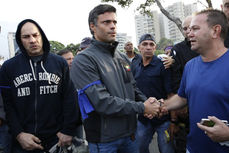 Opposition leader Leopoldo Lopez, center, is greeted by a supporter outside La Carlota air base in Caracas, Venezuela, Tuesday, April 30, 2019. Lopez, who had been under house arrest for leading an anti-government push in 2014, said he had been freed by soldiers and called for a military uprising. (AP Photo/Ariana Cubillos)