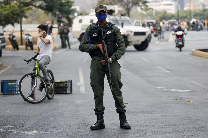 A soldier stands on an avenue leading to La Carlota air base in Caracas, Venezuela, Tuesday, April 30, 2019. Venezuelan opposition leader Juan Guaido has called for a military uprising, in a video shot at the air base showing him surrounded by soldiers and accompanied by detained activist Leopoldo Lopez. (AP Photo/Ariana Cubillos)