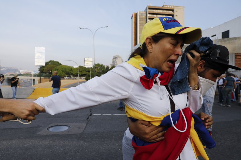 A woman suffocated by tear gas is aid by fellow opponents of President Nicolas Maduro outside La Carlota air base in Caracas, Venezuela, Tuesday, April 30, 2019. Venezuelan opposition leader Juan Guaido appeared in a video with a small contingent of armed soldiers and formerly detained opposition activist Leopoldo Lopez calling for Venezuelans to take to the streets to oust Maduro. (AP Photo/Ariana Cubillos)