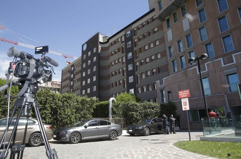 A TV camera and cars are seen outside Milan's San Raffaele hospital where former Italian Premier Silvio Berlusconi arrived, Tuesday, April 30, 2019. Berlusconi is in the hospital suffering from renal colic on the day he planned to present his candidates for European Parliament elections.(AP Photo/Luca Bruno)