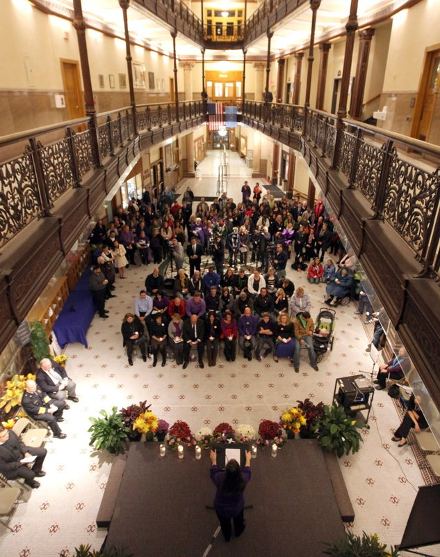 FILE - In this Oct. 21, 2013, file photo, people fill the Milwaukee City Hall rotunda during a vigil marking the one-year anniversary of the Azana Salon & Spa shooting in Brookfield, Wis. Wisconsin's Supreme Court dismissed a lawsuit Tuesday, April 30 2019, alleging a firearms website that enabled a man to illegally purchase the pistol he used in a mass shooting at a suburban Milwaukee spa six years ago is liable in the killings, ruling that federal law grants the site operators immunity. (Mike De Sisti/Milwaukee Journal-Sentinel via AP, File0