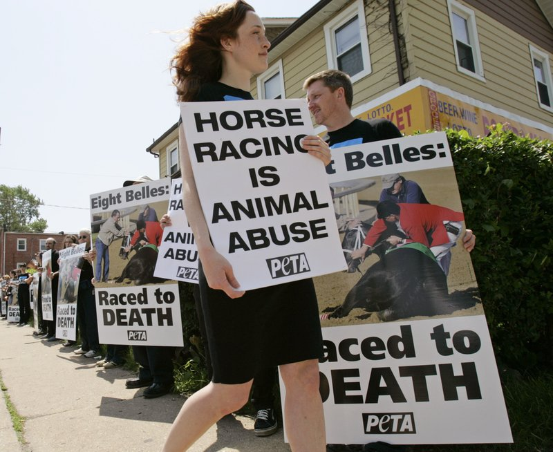 FILE - In this May 17, 2009, file photo, Nicole Matthews holds a placard as she walks past her fellow PETA protesters outside Pimlico Race Course as they call attention to the death of Kentucky Derby second placed horse, Eight Belles, who was euthanized following the race, as they protest before the 133rd Preakness horse race in Baltimore. Horse racing finds itself under intense scrutiny at a time of year when the Kentucky Derby kicks off the Triple Crown series and interest among the general public is at its highest. The deaths of 23 horses over three months at Santa Anita in California have roiled an industry already battered by declining attendance, increased competition for gambling dollars, and the ire of animal rights activists.(AP Photo/Mel Evans, File)
