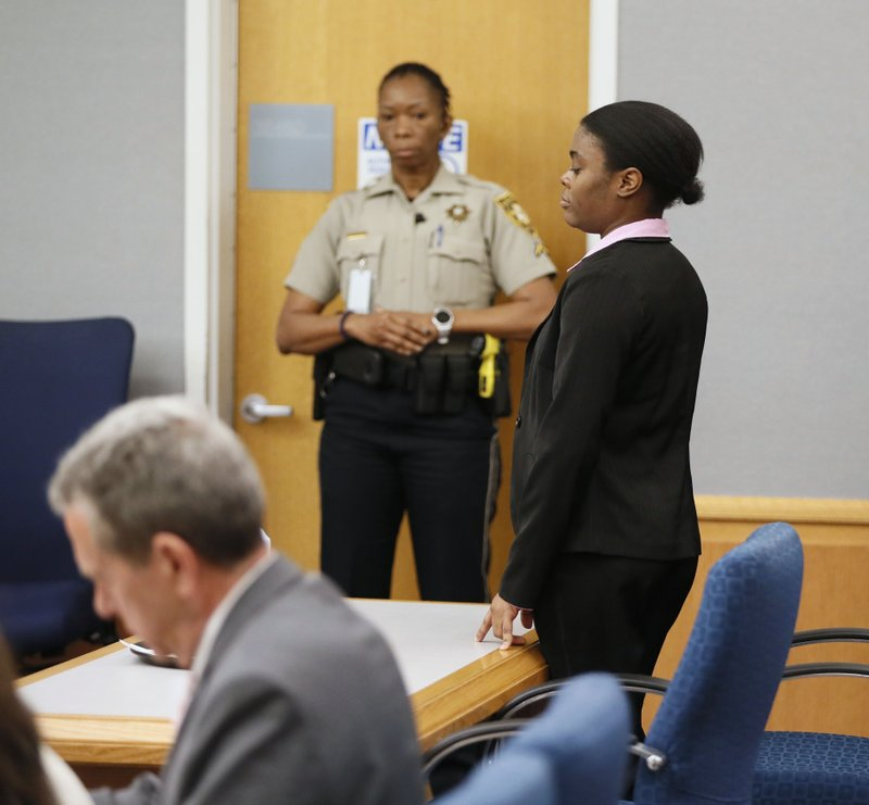 Tiffany Moss stands as her execution date is set, Tuesday, April 30, 2019, in Lawrenceville, Ga. Moss, who found guilty Monday of all counts including murder, cruelty to children and trying to conceal the death of 10-year-old Emani Moss by burning her body in a trash can in 2013, was sentenced to death. (Bob Andres/Atlanta Journal-Constitution via AP)
