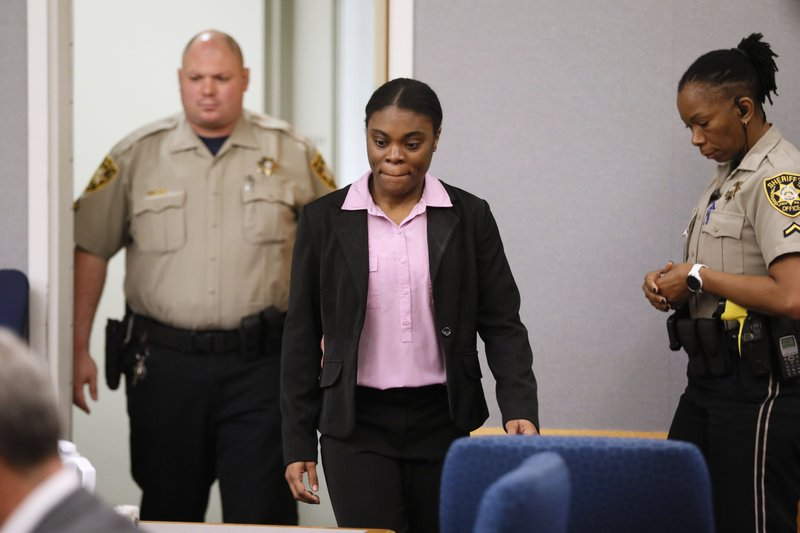 Tiffany Mossenters courtroom for her sentencing, Tuesday, April 30, 2019, in Lawrenceville, Ga. Moss, who found guilty Monday of all counts including murder, cruelty to children and trying to conceal the death of 10-year-old Emani Moss by burning her body in a trash can in 2013, was sentenced to death. (Bob Andres/Atlanta Journal-Constitution via AP)