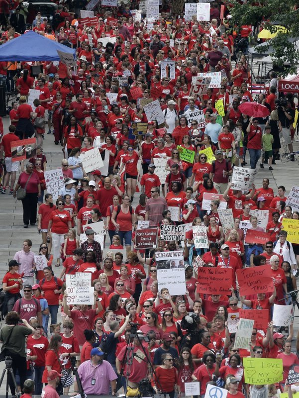 In this May 16, 2018 file photo, participants make their way towards the Legislative Building during a teachers rally at the General Assembly in Raleigh, N.C. North Carolina teachers who are holding their second rally in a year say there's a simple reason why they're doing it: because it works. Educators will gather Wednesday, May 1, 2019, in Raleigh in support of higher pay and other issues. Last year's rally attracted an estimated 20,000 people.(AP Photo/Gerry Broome, File)