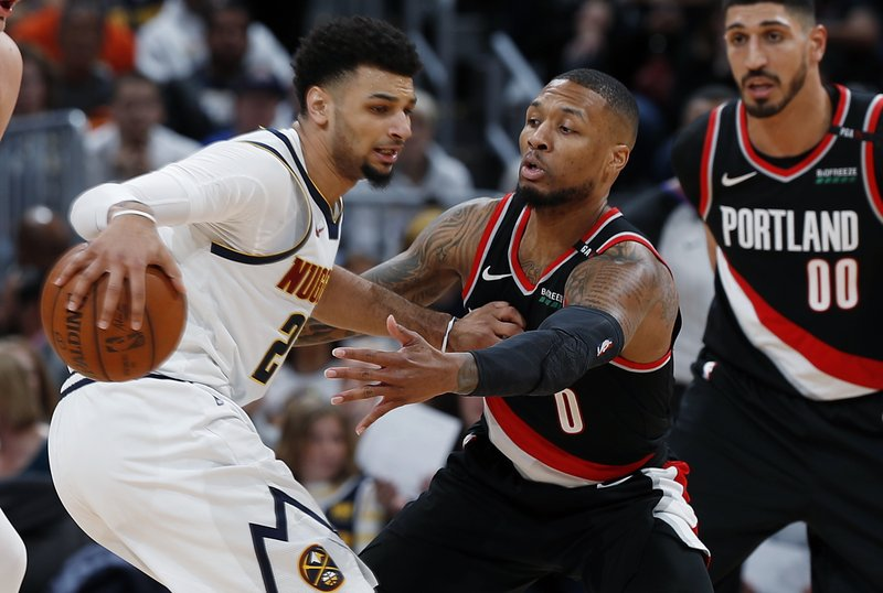 Denver Nuggets guard Jamal Murray, left, looks to pass the ball as Portland Trail Blazers guard Damian Lillard defends in the second half of Game 1 of an NBA basketball second-round playoff series, Monday, April 29, 2019, in Denver. The Nuggets won 121-113. (AP Photo/David Zalubowski)