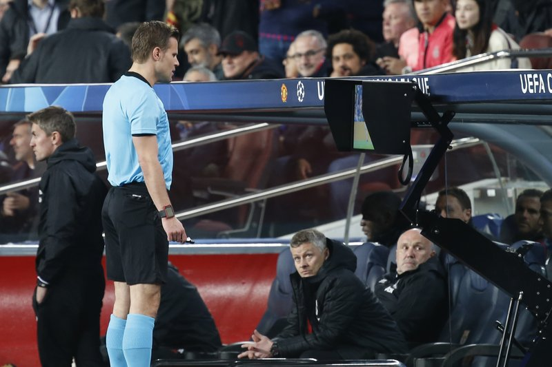 Manchester United coach Ole Gunnar Solskjaer, bottom, watches German referee Felix Brych as watching the VAR monitor during the Champions League quarterfinal, second leg, soccer match between FC Barcelona and Manchester United at the Camp Nou stadium in Barcelona, Spain, Tuesday, April 16, 2019. (AP Photo/Joan Monfort)