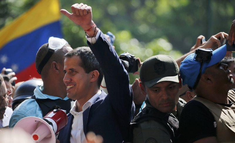 Venezuela's self-proclaimed president Juan Guaido gives a thumbs up amid supporters in Altamira Plaza in Caracas, Venezuela, Tuesday, April 30, 2019. Guaido took to the streets with a small contingent of heavily armed troops early Tuesday in a bold and risky call for the military to rise up and oust President Nicolas Maduro. (AP Photo/Fernando Llano)
