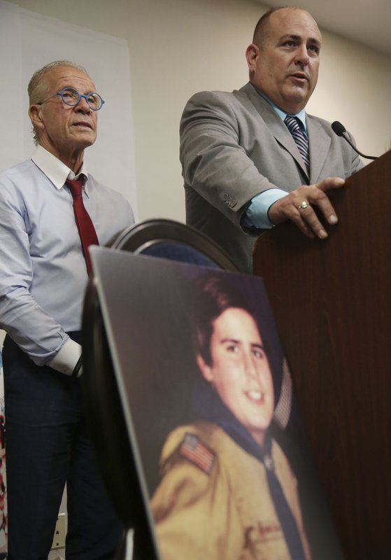 A picture of Richard Halvorson as a boy scout in 1982, when he was 11-years-old, is displayed while Halvorson, right, and attorney Jeff Anderson speak during a news conference in Newark, N.J., Tuesday, April 30, 2019. Halvorson is alleging sexual abuse in a lawsuit filed against the Boy Scouts of America. (AP Photo/Seth Wenig)
